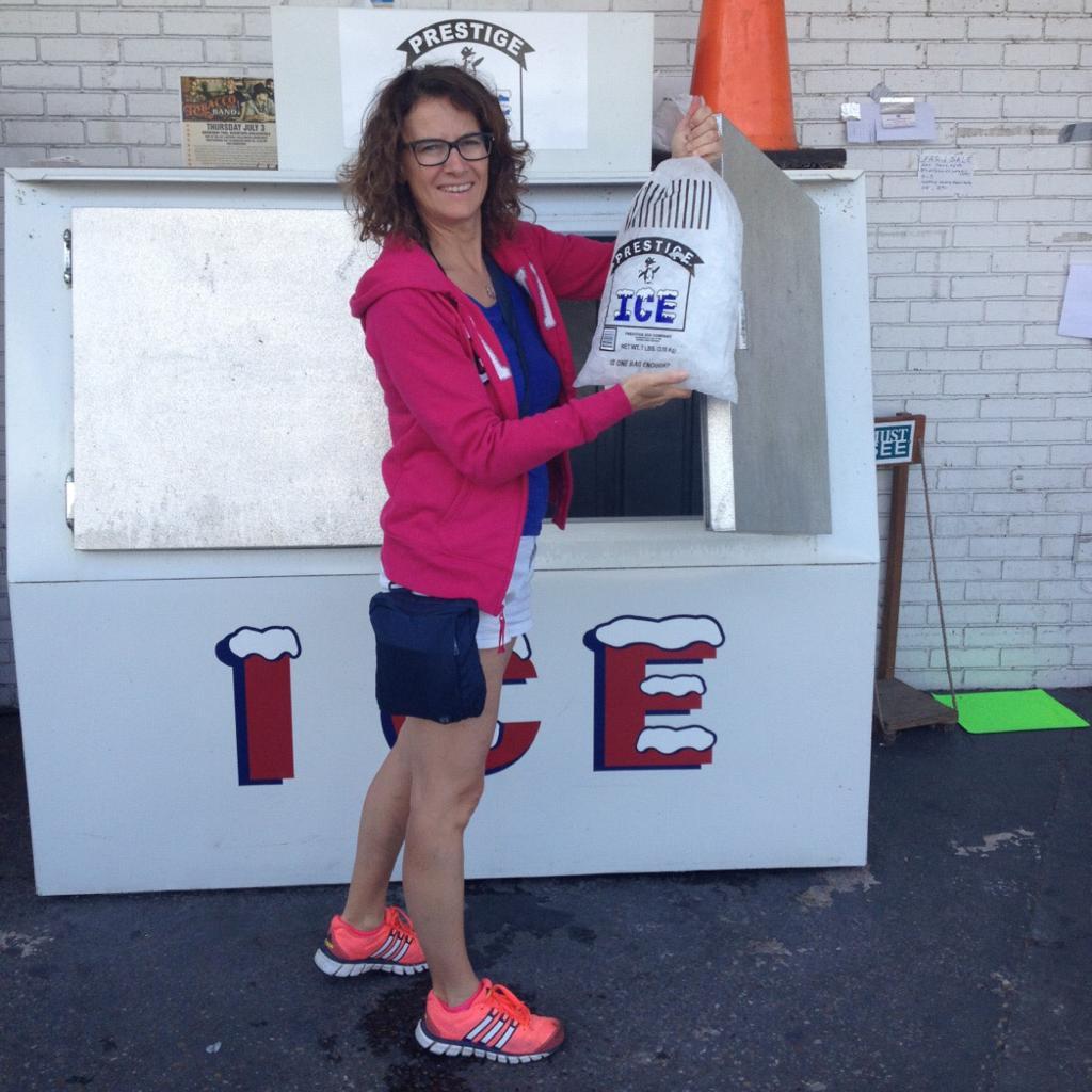 una donna vicino alla macchina del ghiaccio con in mano il sacco del ghiaccio in America